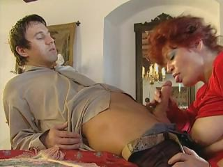 redhead elderly spreads her stockinged feet and